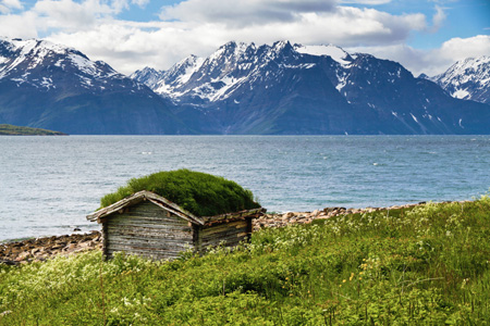 A small hut with a grass roof overlooking a lake and mountains