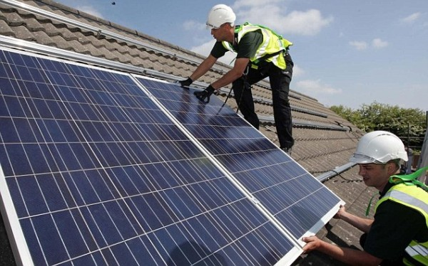 Workmen installing solar panels on a UK roof.